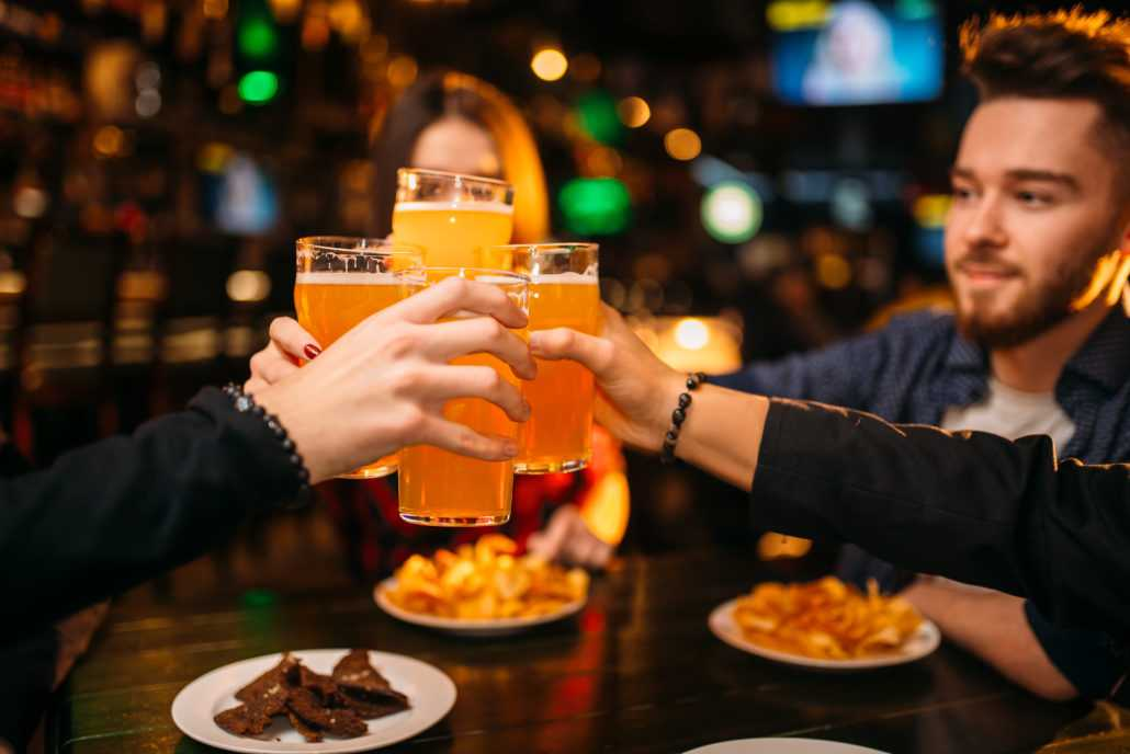 Fun company raised their glasses with beer in a sport bar, happy football fans